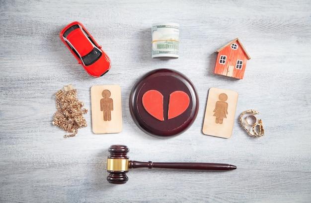 Symboles en bois masculins et féminins, marteau, maison, voiture, cœur brisé et marteau de juge.