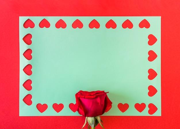 Symboles de coeur sur papier bleu près de rose