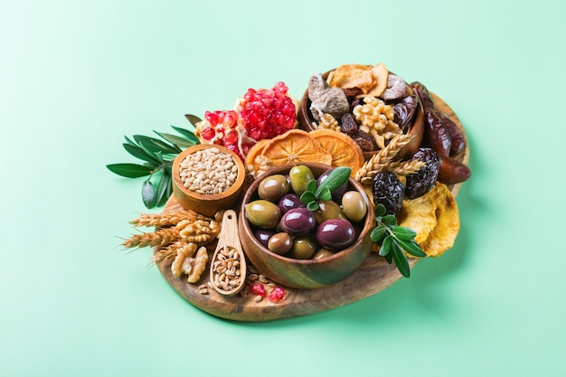 Symboles de la fête judaïque tu bishvat, rosh hashana nouvel an des arbres. mélange de fruits secs, date, figue, raisin, orge, blé, olive, grenade sur une table verte. copier l'arrière-plan de l'espace