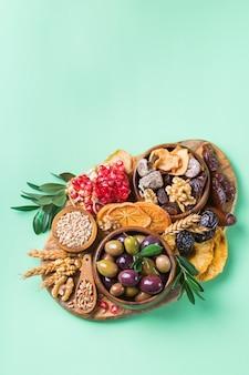 Symboles de la fête judaïque tu bishvat, rosh hashana nouvel an des arbres. mélange de fruits secs, datte, figue, raisin, orge, blé, olive, grenade. copiez l'espace plat fond vert