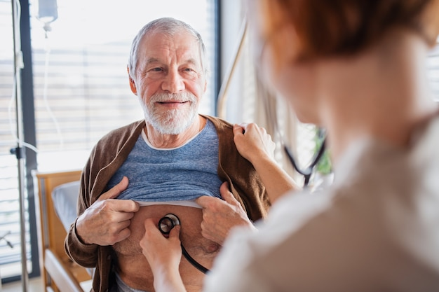 Une sympathique femme médecin examinant une patiente âgée avec un stéthoscope au lit à l'hôpital.