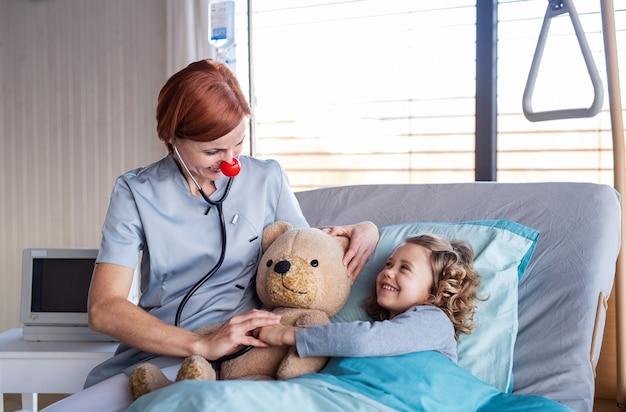 Sympathique femme médecin avec stéthoscope examinant une petite fille au lit à l'hôpital.