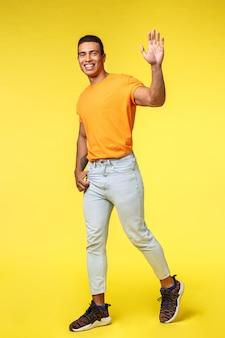 Sympathique jeune bel homme souriant, agitant la main levée