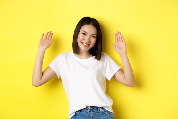 Sympathique jeune femme asiatique disant bonjour, levant les mains vides et souriant, vous saluant, debout sur le jaune.