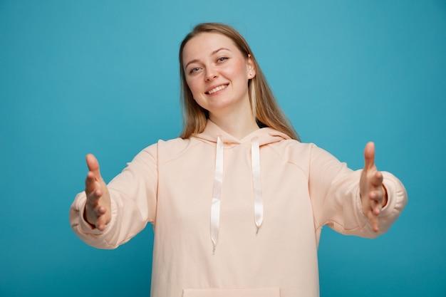 Sympathique jeune femme blonde faisant un geste de bienvenue