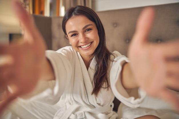 Sympathique jeune femme en peignoir blanc levant les mains grandes ouvertes donnant des câlins gratuits