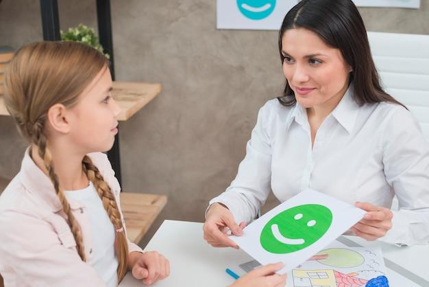 Sympathique jeune femme psychologue et fille tenant la carte du visage émotion heureuse