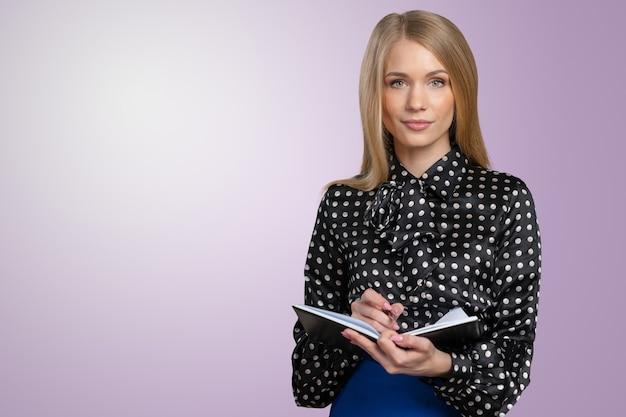 Sympathique jeune femme souriante avec le presse-papier et stylo