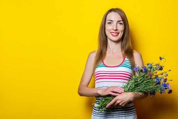 Sympathique jeune fille souriante avec un bouquet de fleurs sauvages