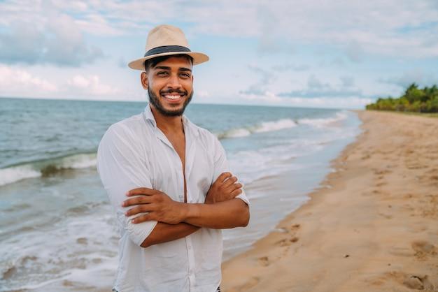 Sympathique jeune homme latino-américain avec les bras croisés sur la plage, portant un chapeau