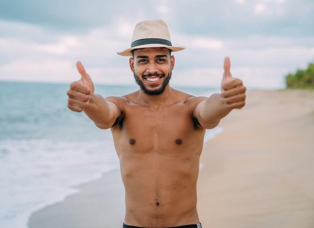 Sympathique jeune homme latino-américain faisant un geste de pouce en l'air