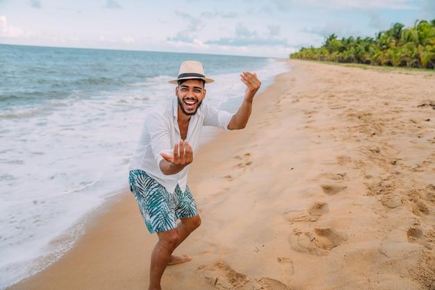 Sympathique jeune homme latino-américain invitant à venir au brésil, confiant et souriant faisant un geste avec sa main, étant positif et amical