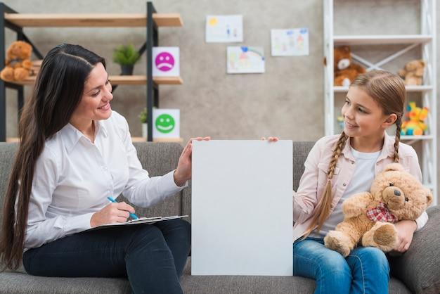 Sympathique psychologue et petite fille tenant une pancarte blanche assis sur un canapé