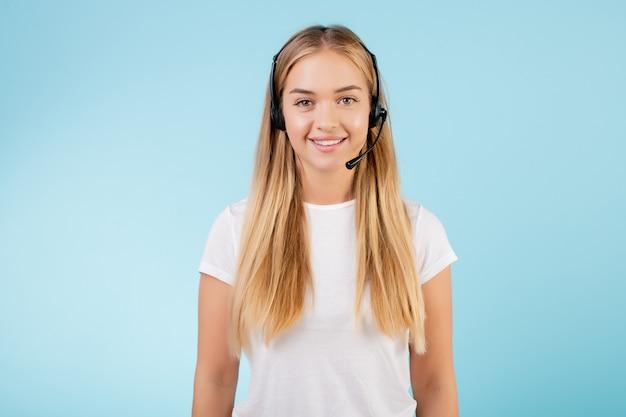 Sympathique souriant opérateur de centre d'appel blonde avec casque isolé sur bleu