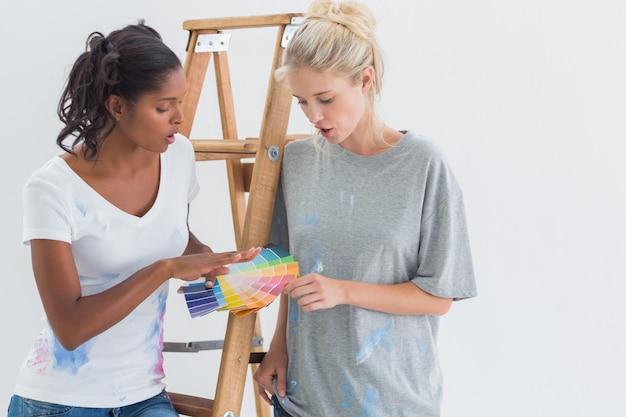 Sympathiques colocataires choisissant la couleur du mur