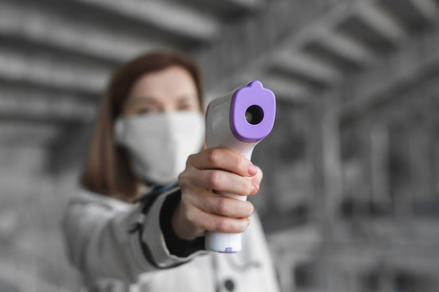 Symptômes du coronavirus, une femme portant un masque médical mesure la température corporelle. médecin regarde un thermomètre numérique sans contact isométrique dans ses mains, concept de mise en quarantaine covid-19