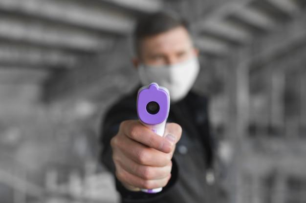 Symptômes du coronavirus, l'homme dans un masque médical mesure la température corporelle. docteur regarde un thermomètre numérique sans contact isométrique dans ses mains, concept de mise en quarantaine covid-19