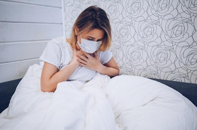 Les symptômes de la maladie à coronavirus (covid-19) sont le nez qui coule, le mal de gorge, la toux et la fièvre. jeune femme malade d'une infection virale à coronavirus propageant le virus corona. patient couché dans son lit à la quarantaine à domicile