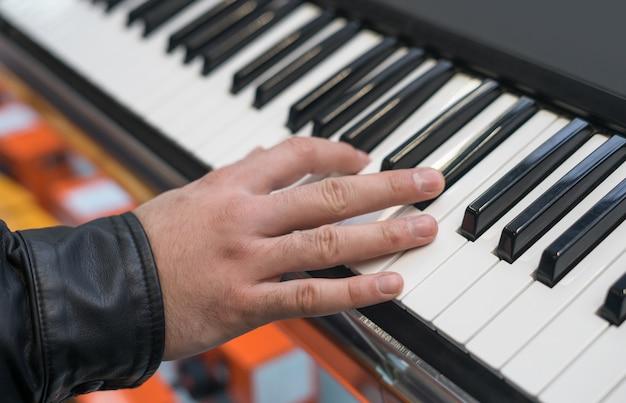 Synthétiseur de clavier de piano avec la main jouant dessus