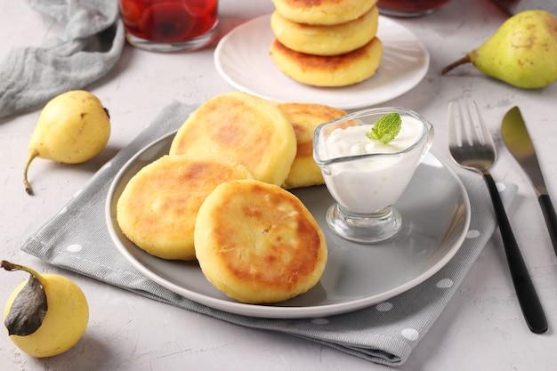 Syrniki plat traditionnel ukrainien fait maison avec de la crème sure sur plaque grise sur fond clair