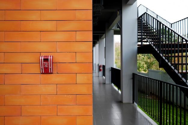 Système d'alarme incendie installé sur un mur de briques à l'extérieur du bâtiment.