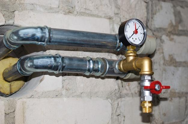 Système de chauffage industriel. capteur de pression sur le réducteur de pression d'eau chaude. pose de nouveaux tuyaux. fermer.