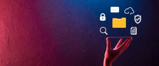 Système de gestion de documents dms. l'homme d'affaires détient l'icône du dossier et du document. logiciel d'archivage, de recherche et de gestion des fichiers et des informations d'entreprise. concept de technologie internet. sécurité numérique