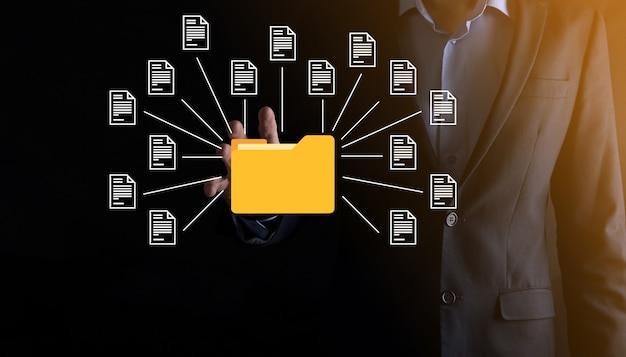 Système de gestion de documents dms. l'homme d'affaires détient l'icône du dossier et du document. logiciel d'archivage, de recherche et de gestion des fichiers et des informations d'entreprise. concept de technologie internet. sécurité numérique.
