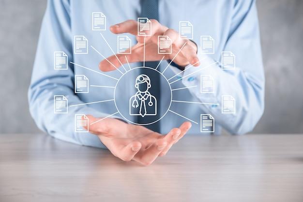 Système de gestion de documents dms. l'homme d'affaires détient l'icône du médecin et du document. logiciel d'archivage, de recherche et de gestion des fichiers et des informations d'entreprise. concept de technologie internet. sécurité numérique.