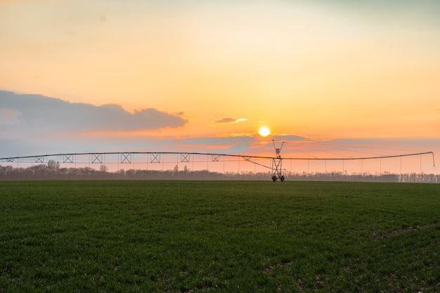 Système d'irrigation en fonctionnement pendant un coucher de soleil d'été doré.