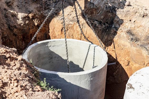 Système de piston hydraulique de la pelle avec un godet, descendant dans la fosse sur des câbles en acier anneau d'égout en béton. construction ou réparation de maison d'égout.