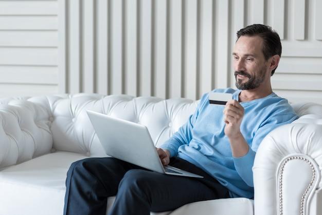 Sytème bancaire électronique. agréable homme adulte joyeux tenant une carte de crédit et effectuant un paiement électronique tout en achetant quelque chose en ligne