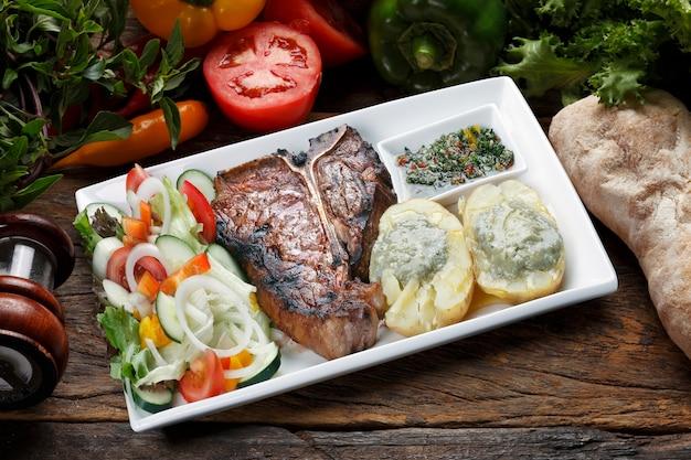 T bone steak avec salade de pommes de terre et légumes