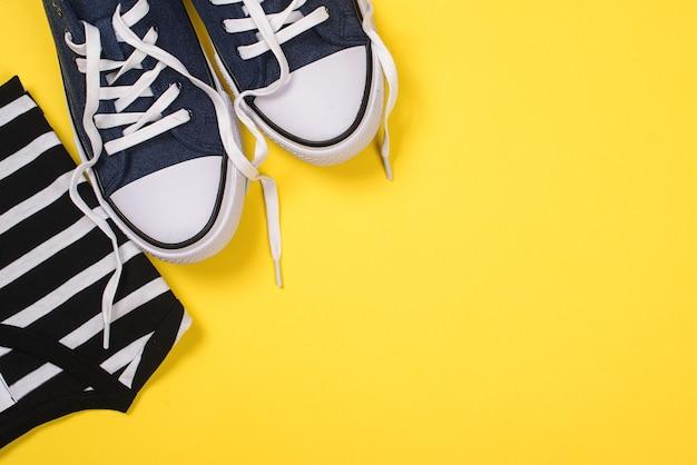 T-shirt et baskets sur jaune, pose plate
