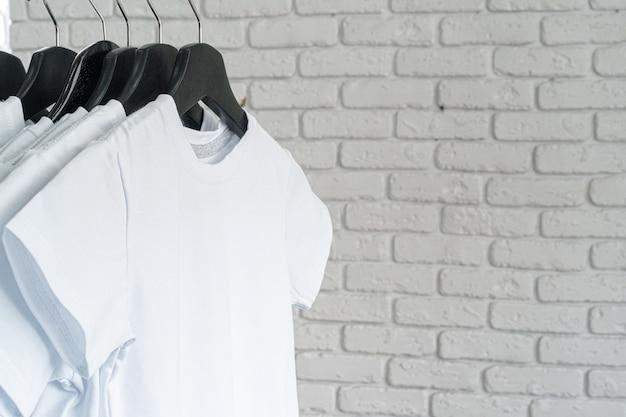 T-shirt blanc accroché sur un cintre contre le mur de briques, espace copie