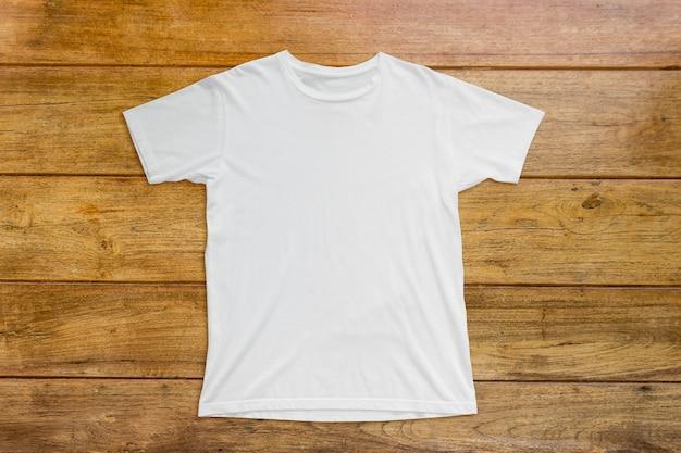 T-shirt blanc sur plancher en bois