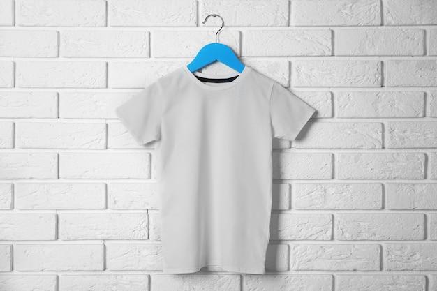 T-shirt blanc vierge contre le mur de briques