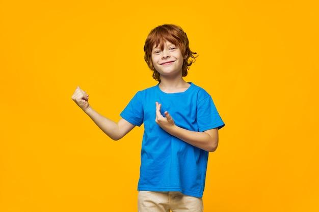 T-shirt bleu garçon cheveux roux jaune taches de rousseur isolées lutte montrer le poing sur le côté