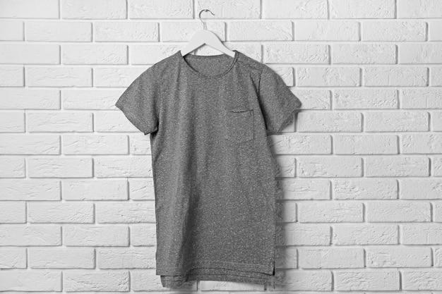 T-shirt gris blanc contre le mur de briques