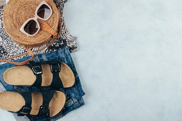 T-shirt à imprimé animalier, short en jean bleu, sac en rotin à la mode, lunettes de soleil.