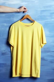 T-shirt jaune blanc contre le mur de grunge