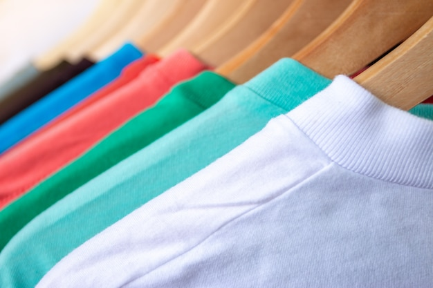 T-shirt de mode sur le rack de vêtements - gros plan du placard coloré lumineux sur des cintres en bois dans le placard du magasin.