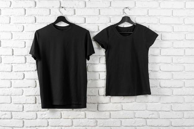 T-shirt noir accroché sur un cintre contre le mur de briques, vue de face