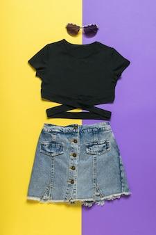 Un t-shirt noir, des lunettes noires et une jupe en jean sur une surface jaune et violette