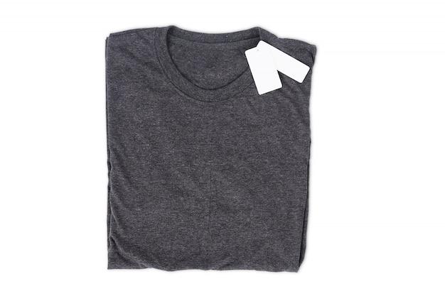T-shirt plié avec étiquette isoler sur fond blanc avec un tracé de détourage pour la maquette de conception