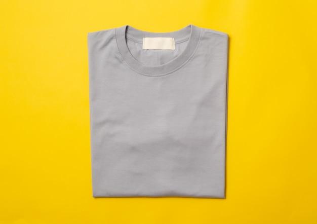 T-shirt plié gris isolé sur fond jaune.