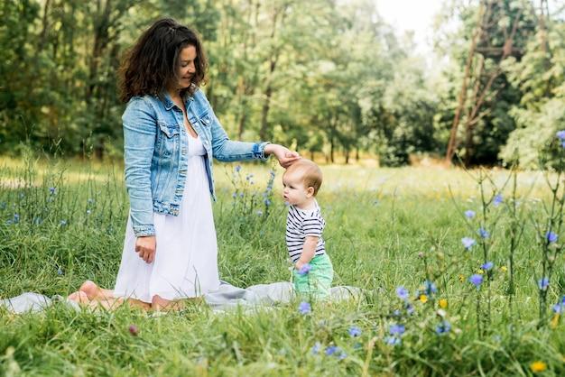 T-shirt rayé mignon bébé garçon caucasien. pique-nique dans le parc d'été. premiers pas.