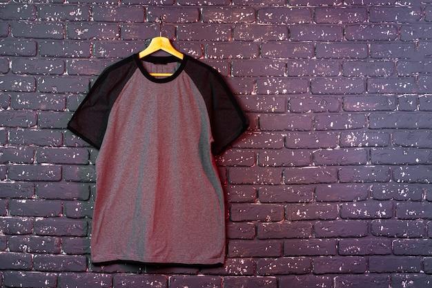 T-shirt uni noir accroché à un cintre, espace copie