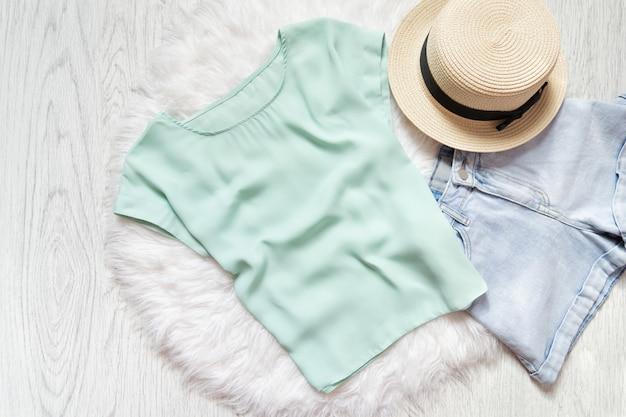 T-shirt vert menthe, jean bleu et chapeau de paille sur fourrure blanche. collage de mode