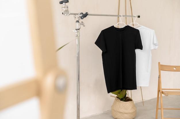 T-shirts blancs et noirs sur des cintres pour la présentation du design